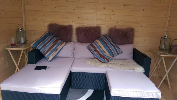 shed interior with l-shaped sofa and cushions
