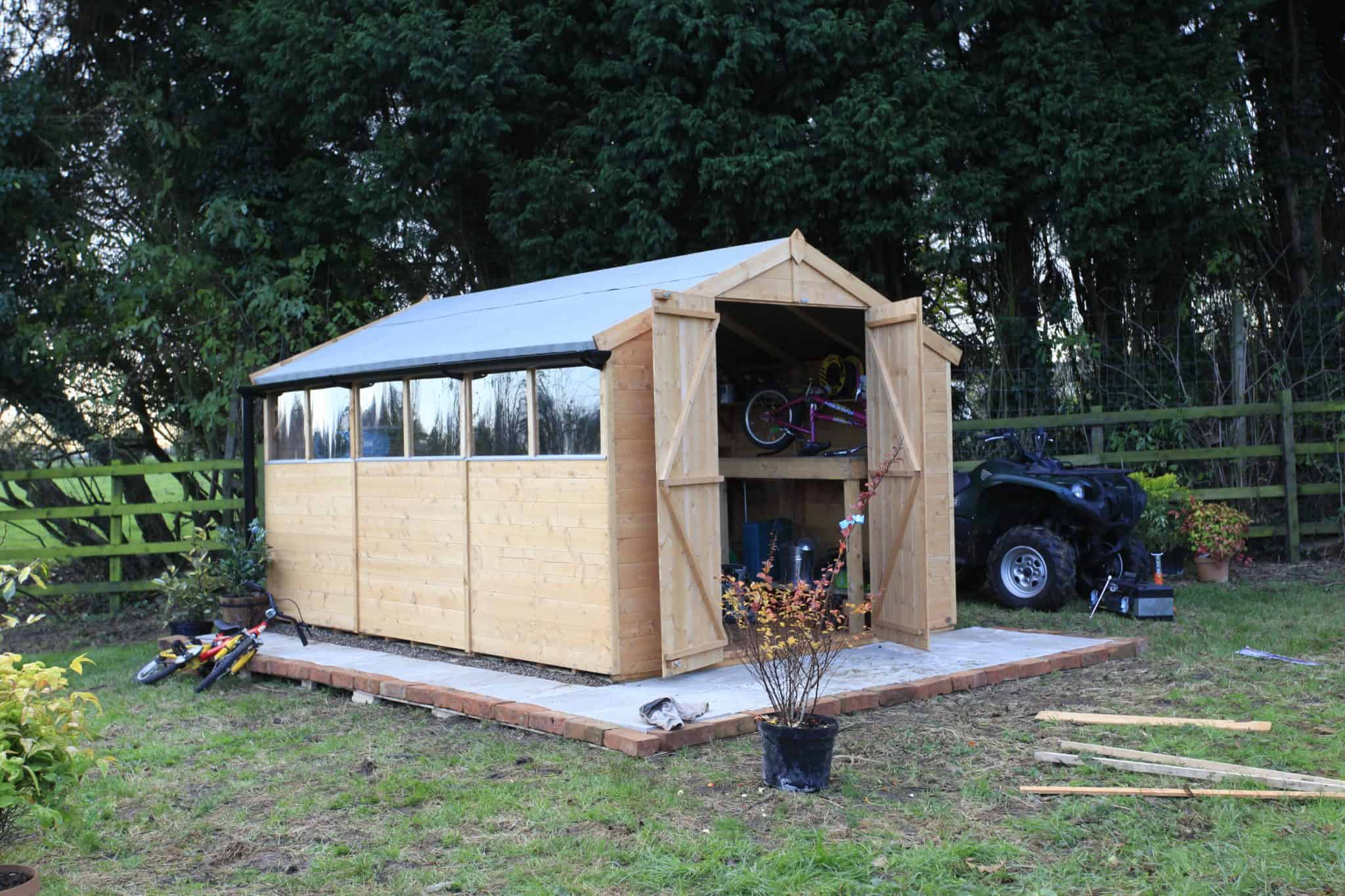 Apex roof shed with open double doors on a concrete slab with pot plant in front