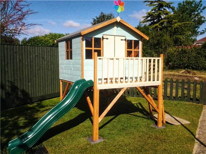 Tower playhouse with flag and slide on grass