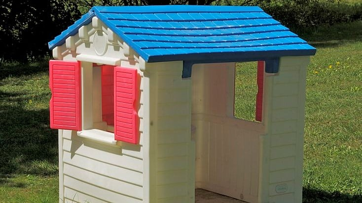 plastic playhouse in white and blue with red shutter windows on grass