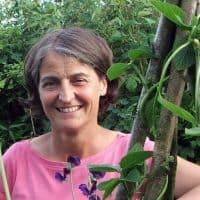 Sally Nex stood smiling behind a vine