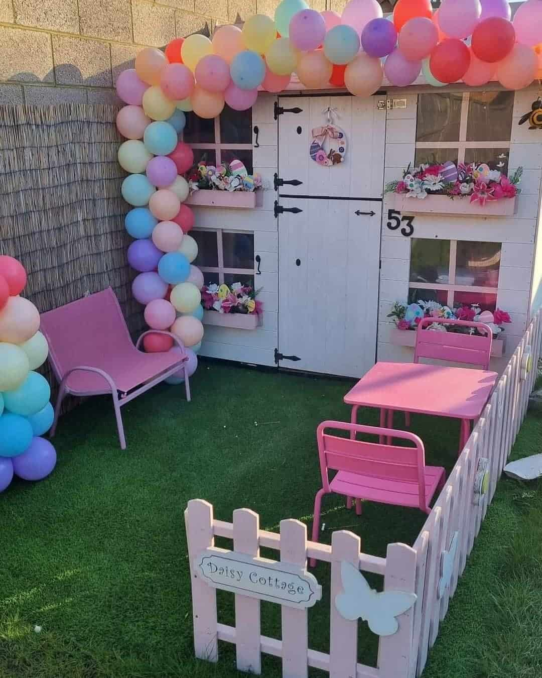 two storey barn door playhouse with picket fence painted white on astro turf with balloon arch around the door