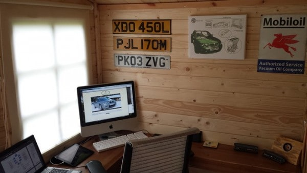 shed interior with number plates on the wall and a computer