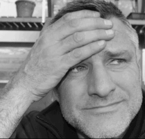 black and white photo of David Marsden of The Anxious gardener with a frown and his hand to his head