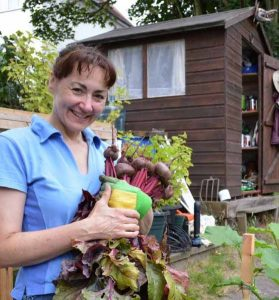 Sandra Lawrence of The Event Gardener in front of a shed smiling and holding vegetables