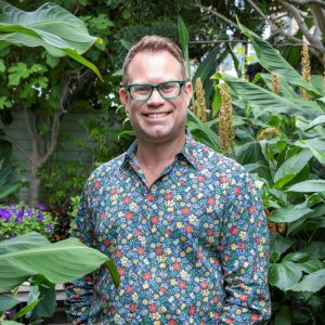 Dan Cooper in a patterned shirt smiling stood among plants