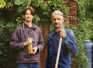Nick Moyle and Richard Hood of Two Thirsty Gardeners holding a rake and a bottle