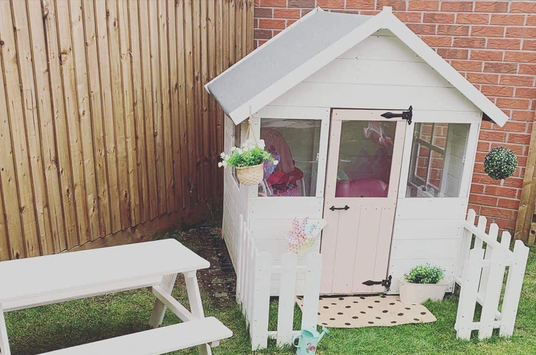 Single storey pent roof playhouse painted white with small bench and picket fence on turf