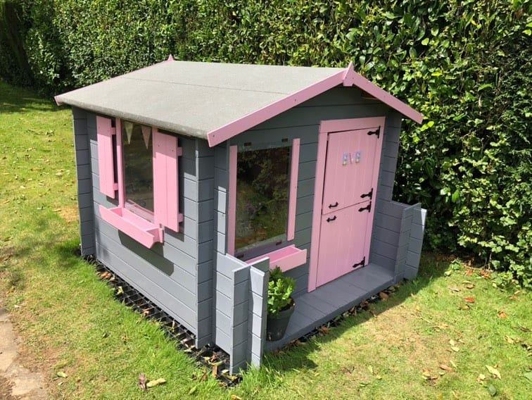 single storey pent roof playhouse with small porch painted pink and grey on grass