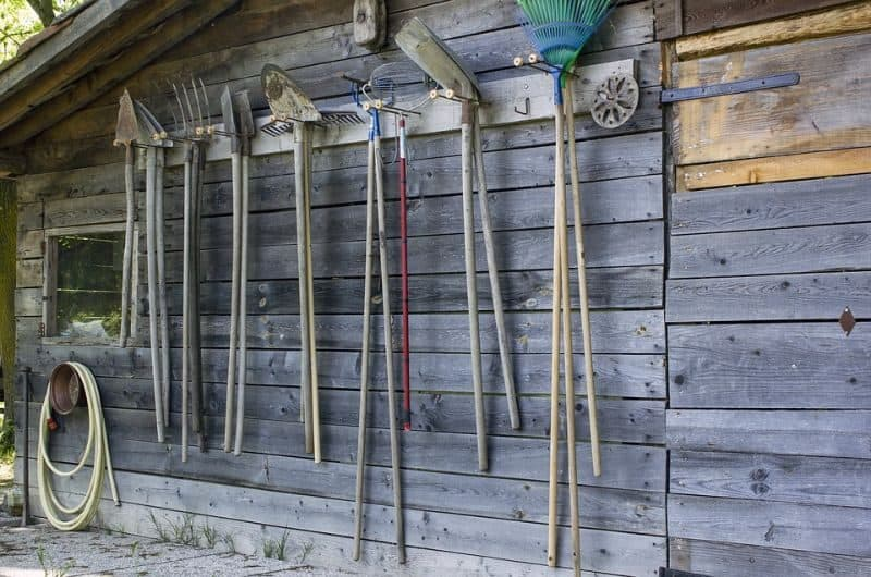wooden timber shed with garden tools hanging up