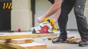 Man bent over holding a circular Dewalt saw cutting timber