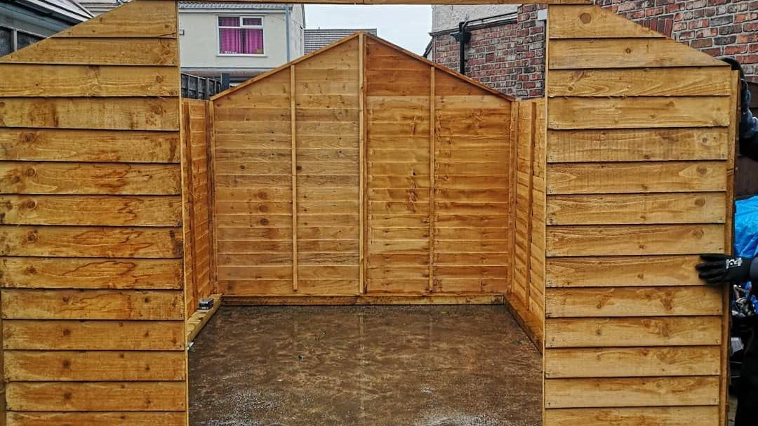shed frame without roof being constructed on a wet patio facing front on