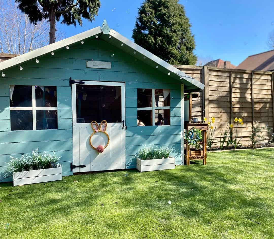 pent roof single storey playhouse on grass painted blue and white