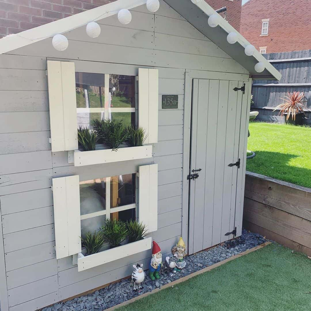 two storey pent roof playhouse with shuttered windows and window planters on astro turf on sunken level of garden