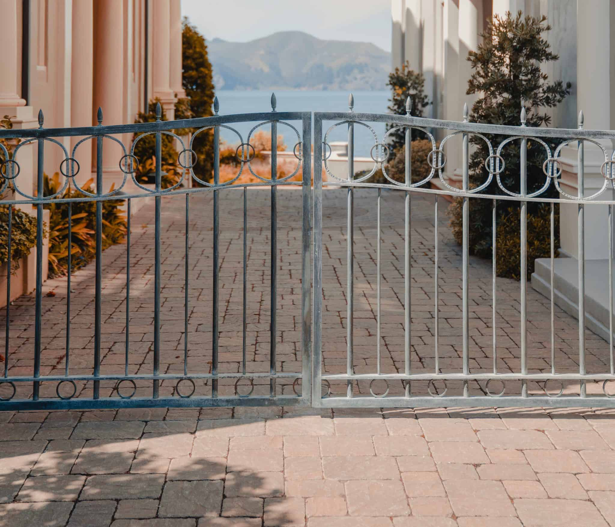 iron gates at the end of a city lane looking past European houses to the sea
