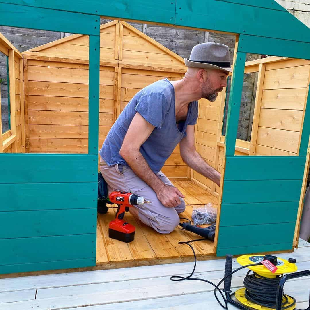 @ourbathhome with man building teal painted playhouse panels