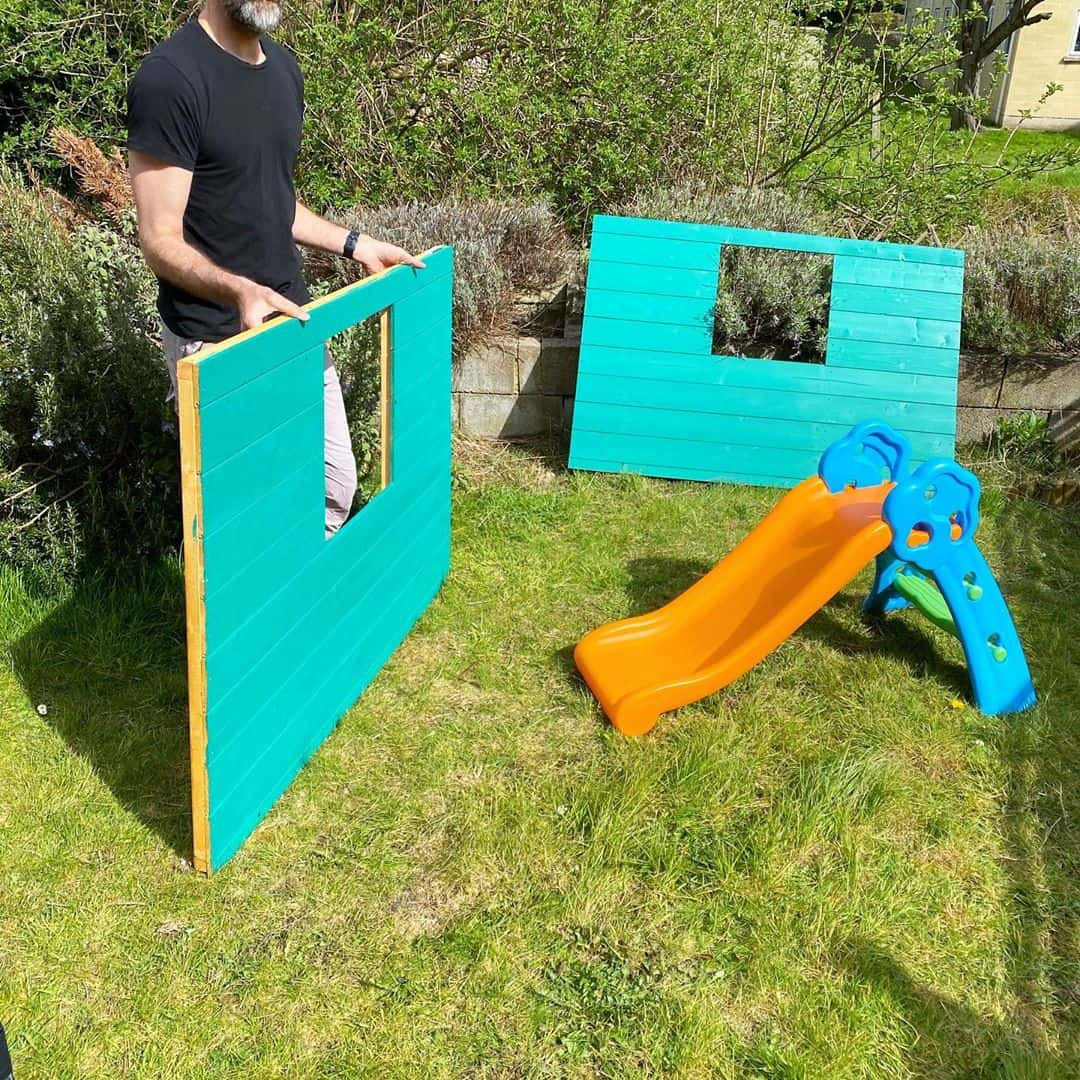 @ourbathhome with man building teal painted playhouse panels on grass