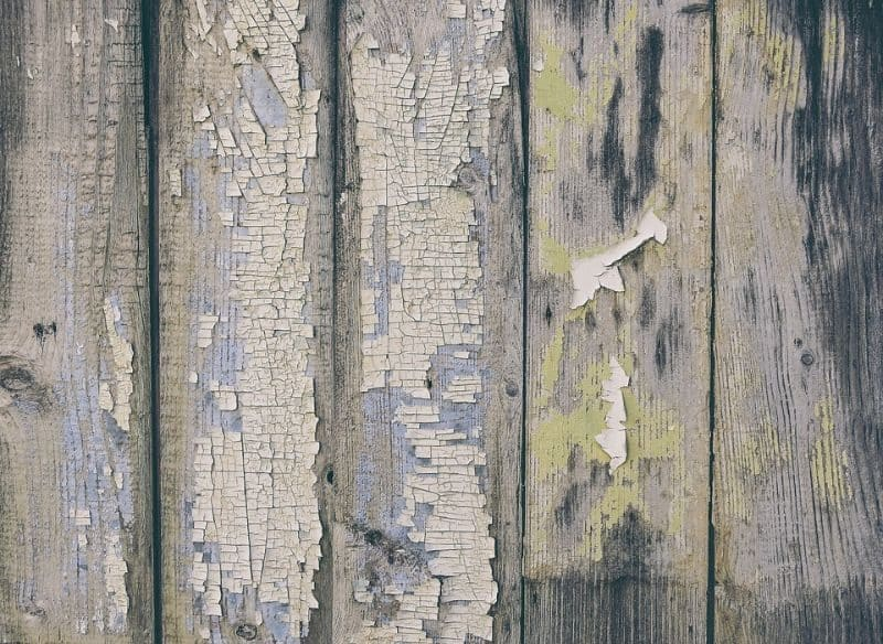 vertical wooden panels with chipped and flaking paint