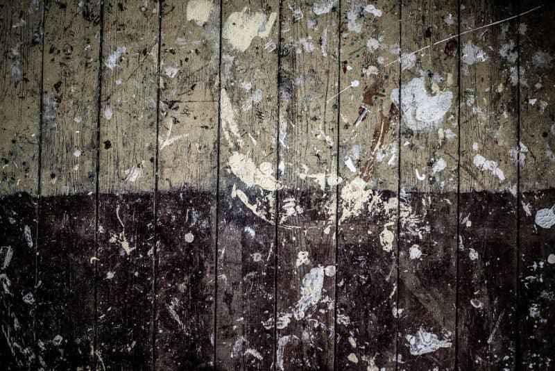 wooden panels with bottom half painted black and splotches of paint on them