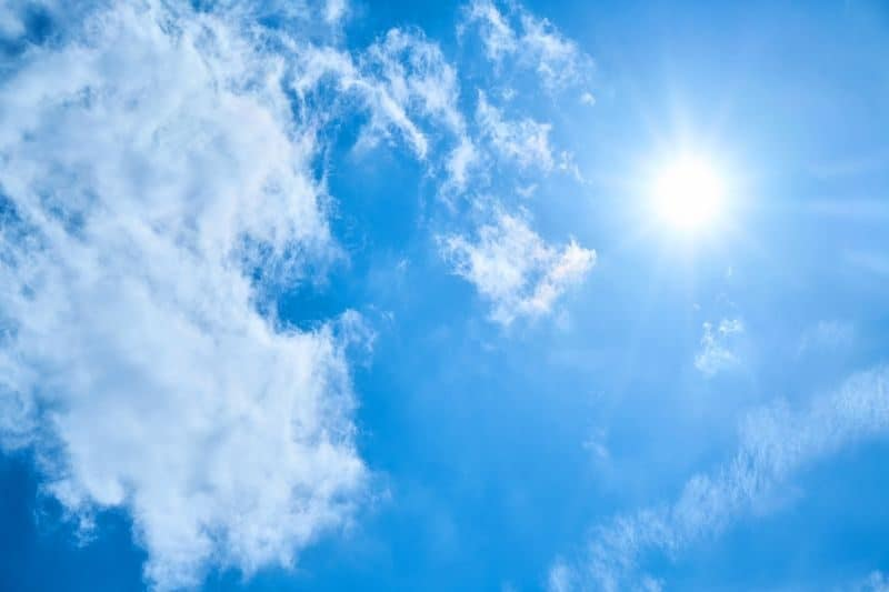 sun shining white and bright in a cloud-flecked blue sky