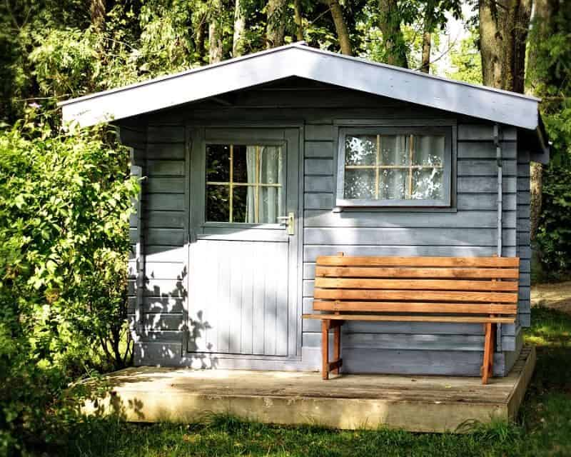 blue timber shed in a clearing on a wooden pallet with a bench on the porch