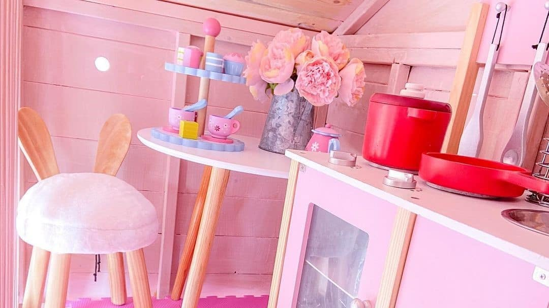 pink playhouse interior with pink cabinets, stool, flowers