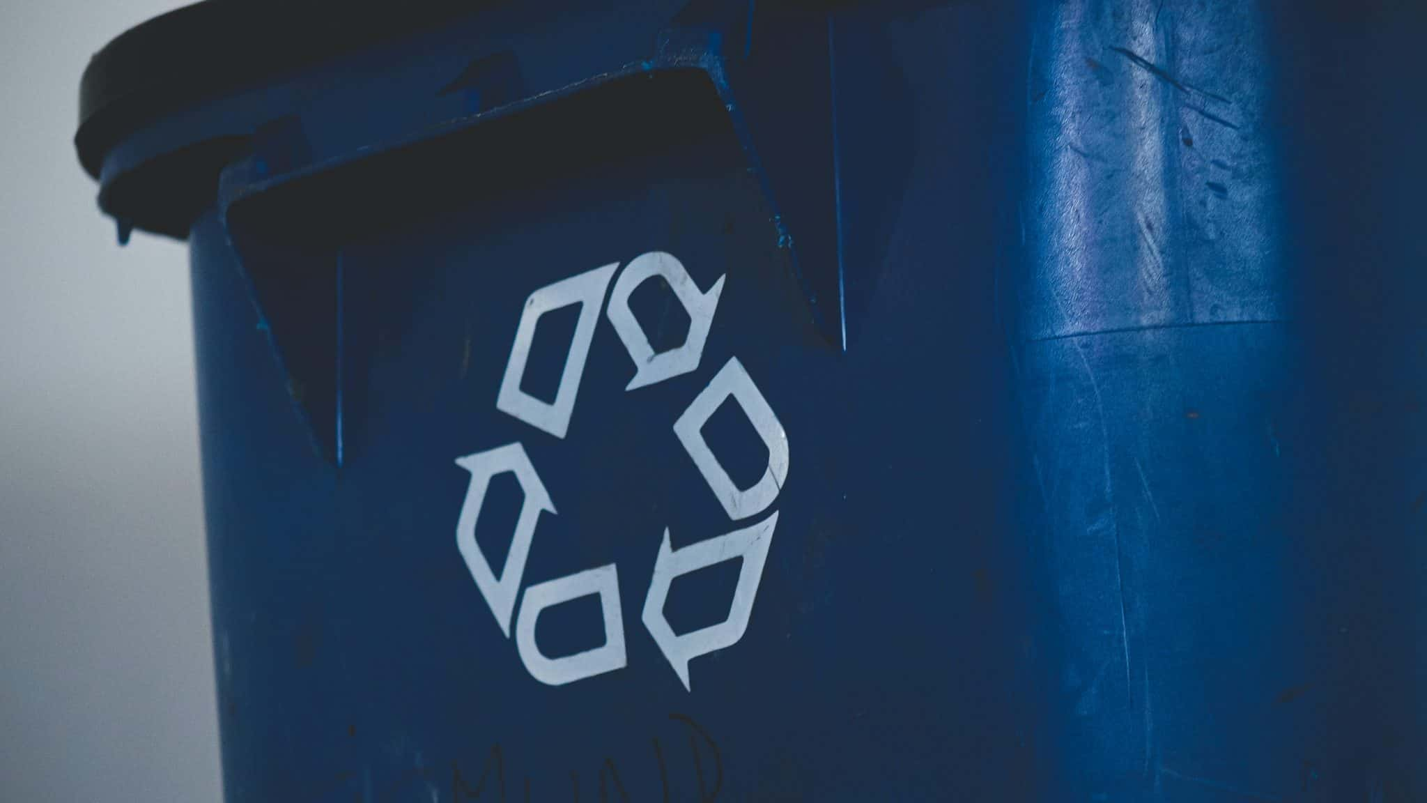 Blue recycling bin focused on recycle logo