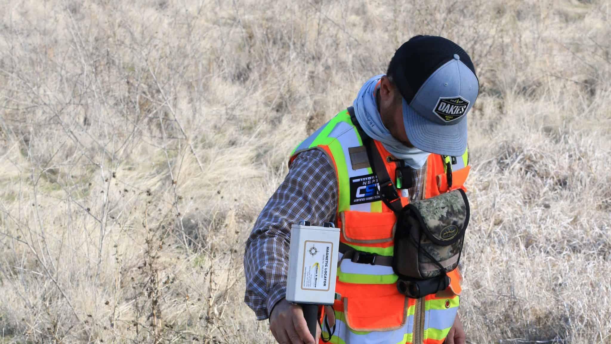 man in UV vest surveying land