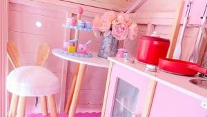 pink children's wooden playhouse interior with pink stool, table, and flowers