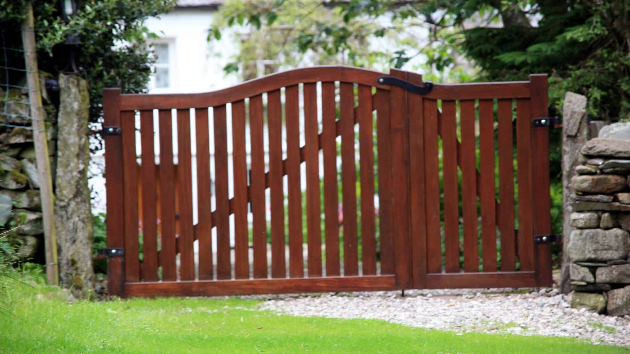 wooden sliding driveway gate on gravel path with lawn