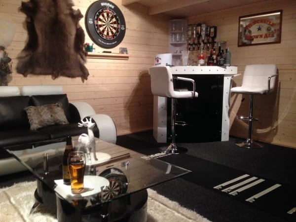 shed interior with animal pelts and dartboard on the wall and small corner bar