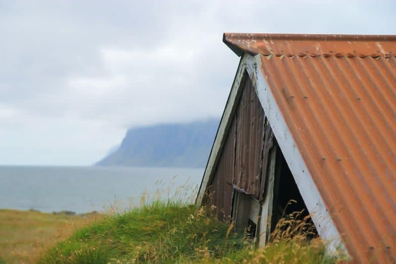 shed roof and eaves semi-obscured by green grass with sea, clouds, and cliffs in the distance