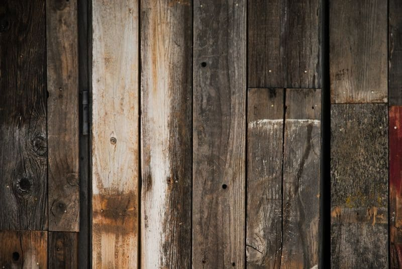 vertically wooden planks or cladding at different shades and stages of discolouration