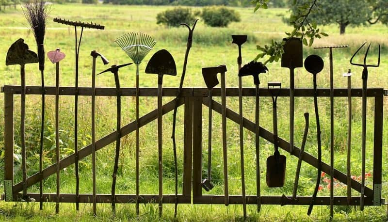 garden tools like hoes, pitchforks and rakes hung from pegs on a wooden gate in a field