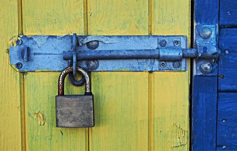 yellow and blue painted wooden shed with a bolt lock and padlock