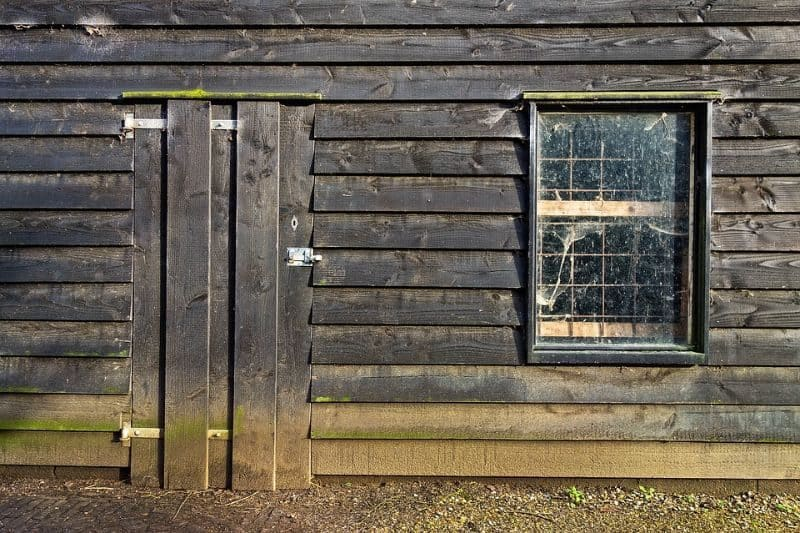 exterior of large dark wood wooden shed with vertical planks across the doors and dirty window with spider webs