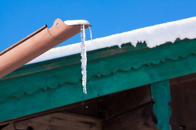 frozen water forming an icicle coming out of a gutter in front of a snow-covered wooden roof