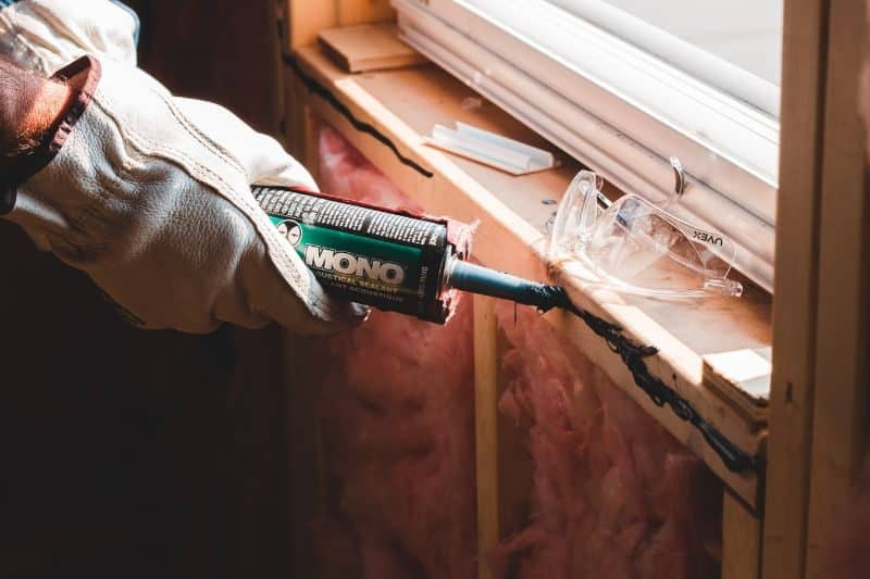 gloves hands caulking the interior of a window frame with black silicone